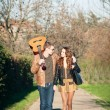 Romantic young couple walking with guitar outdoors in a park — Stock Photo