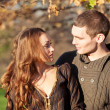Romantic young couple looking each others outdoors in autumn park — Stock Photo #18446531