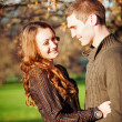 Foto Stock: Romantic young couple playing outdoors in autumn park