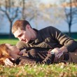 Foto Stock: Young couple in a romantic mood lying down outdoors in a park