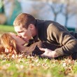 Romantic young couple kissing lying down outdoors in autumn park — Stock Photo #18446593
