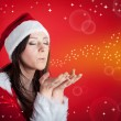 Christmas woman blowing portrait on red background — Stock Photo