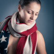 Young woman portrait with american flag scarf against grey background — Stock Photo #18446945