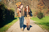 Young couple walking in a romantic mood with guitar outdoors in a park — Stock Photo