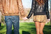 Hand in hand romantic young couple walking outdoors in autumn park — Stock Photo