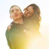 Romantic young couple outdoors with back light — Stock Photo