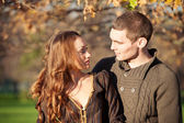 Romantic young couple looking each others outdoors in autumn park — Stock Photo