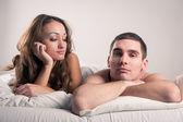 Closeup portrait of a tired young couple lying in bed — Stock Photo