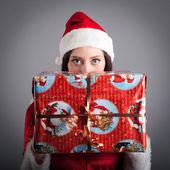 Mulher de natal chapéu santa segurando o presente de natal vermelho sobre fundo cinzento — Foto Stock