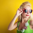 Blonde girl with heart glasses against yellow background — Stock Photo