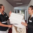 Two chambermaid women talking together during service in a hotel - Stock Photo
