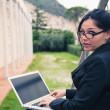 młoda kobieta na zewnątrz przy użyciu komputera typu tablet — Zdjęcie stockowe