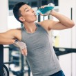 Young asimhaving rest drinking beverage in gym — Stock Photo #18708569