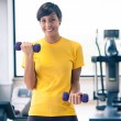 Young girl exercising with dumbbells in the gym - Stock Photo