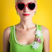 Blond meisje met een hart bril tegen gele achtergrond — Stockfoto