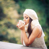 Young woman drinking from a cup outdoors in the nature — Stock Photo