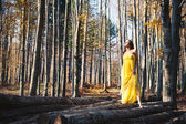 美丽的年轻女子,与户外在树林里的黄色礼服画像 — 图库照片