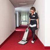 Chambermaid woman cleaning in a hotel with vacuum cleaner — Stock Photo