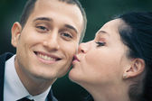 Young woman kissing happy businessman — Foto Stock