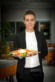 Happy young waitress with food in restaurant — Stock Photo