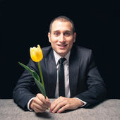 Man waiting his girlfriend at a restaurant with yellow flower — Stockfoto