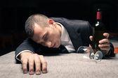 Homme d'affaires jeune ivre senti endormi avec du vin rouge — Photo