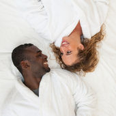 Happy young couple lying in bed looking at each other, top view — Stock Photo