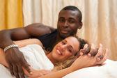 Interracial jeune couple heureux détendu dans son lit. mettre l'accent sur les mains — Photo