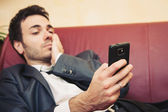 Portrait of tired young businessman typing on cellphone on sofa — Stock Photo
