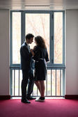 Young couple, businessman and chamber maid, at the window in a house — Stock Photo