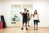 年轻夫妇的哑铃在健身房锻炼 — 图库照片