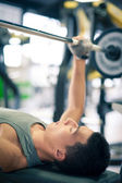 Young man lifting the barbell in the gym — Stock Photo