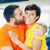 Young couple embracing and kissing at the gym — Stock Photo
