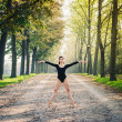 Young beautiful ballerindancing outdoors in parkway with trees — Stock Photo #18836177