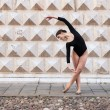 Young beautiful ballerina dancing outdoors in front of Palazzo dei Diamanti in Ferrara, Italy - Stock Photo