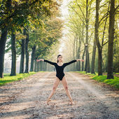 Young beautiful ballerina dancing outdoors in a parkway with trees — Stock Photo