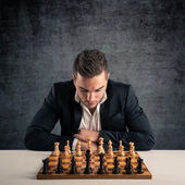 Man playing chess, isolated on dark grunge background — Stock Photo