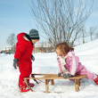 Two little kids - boy and girl - having fun with sledge in the snow — Lizenzfreies Foto