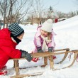 Two little kids - boy and girl - having fun with sledge in the snow — Stock Photo