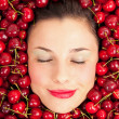 Young girl smiling portrait with closed eyes surrounded by cherries — Stock Photo #19176077