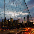Manhattan skyline from the Brooklyn bridge at dusk with cars traffic — Stock Photo