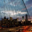 Stock Photo: Manhattan skyline from the Brooklyn bridge at dusk with cars traffic