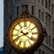 NEW YORK - JUNE 28: Sidewalk clock at 200 Fifth Avenue (1909) with Flatiron building facade - Stock Photo
