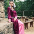 Beautiful girl wearing a burgundy medieval dress. Full body — Stock Photo