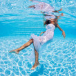 Underwater girl fashion portrait with white dress in swimming pool — Stock Photo