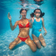 Mother and daughter having fun underwater in swimming pool — Stock Photo