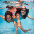 Stock Photo: Mother and daughter having fun underwater in swimming pool