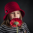 Stock Photo: Little girl smells red daisy flower against black background