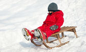 Kid sliding with sledge in the snow — Stock Photo