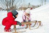 Two little kids - boy and girl - having fun with sledge in the snow — ストック写真